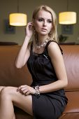 attractive young adult blonde woman in black dress sitting on the brown couch