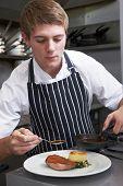 Male Chef Preparing Meal In Restaurant Kitchen