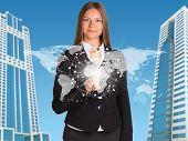 Beautiful businesswoman in suit presses finger virtual sphere