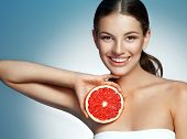 Smiling girl with grapefruit cut in half fruit in hand