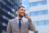 business, technology and people concept - smiling businessman with smartphone talking over office bu