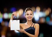 luxury, advertisement, holidays and sale concept - smiling woman with white blank shopping bag over night lights background
