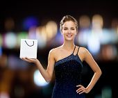 luxury, advertisement, holidays and sale concept - smiling woman with white blank shopping bag over