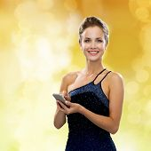 technology, communication, holidays and people concept - smiling woman in evening dress holding smar