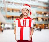 holidays, presents, christmas, childhood and people concept - smiling little girl in santa helper ha