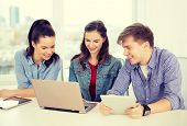 education, technology, school and internet concept - three smiling students with laptop and tablet p