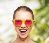 happiness and people concept - portrait of happy teenage girl in pink sunglasses