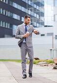 business, hot drinks and people and concept - young serious businessman with paper coffee cup over office building