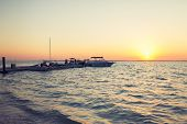 vacation, travel and sea concept - boats moored to pier at sundown