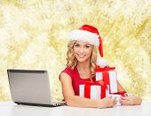 christmas, holidays, technology and people concept - smiling woman in santa helper hat with gifts an