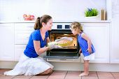 stock photo of oven  - Young happy mother and her adorable curly toddler daughter wearing blue dress baking a pie together in an oven in a white sunny kitchen with modern appliances and devices - JPG