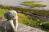 foto of prone  - White women statue prone looking at lake - JPG