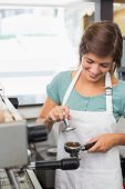 Pretty barista pressing coffee grinds at the coffee shop
