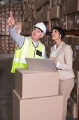 Warehouse worker and manager using laptop in a large warehouse
