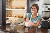 Pretty barista offering cup of coffee smiling at the coffee shop