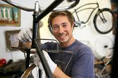 Man in workshop fixing bike frame