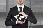 picture of incognito  - businessman in black suit protecting white world map with hands - JPG