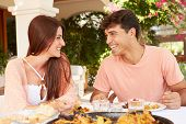 Hispanic Couple Enjoying Outdoor Meal At Home Together