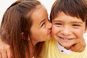 Portrait Of Hispanic Girl Kissing Boy