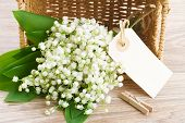 picture of lilly  - lilly of the valley flowers posy in basket with empty paper note on wooden background - JPG