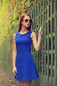 stock photo of versaille  - Redhead girl in sunglasses near fence in Versailles garden  - JPG