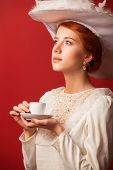 Portrait Of Redhead Edvardian Women With Cup On Red Background.