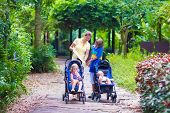 stock photo of mother baby nature  - Young mother with three children - school age boym toddler girl and little baby in stroller walking in a sunny summer park looking at a map