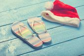Beach Slippers And Christmas Hat On Blue Wood