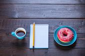 Notebook, Donut And Pencil On Wooden Table.