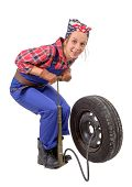 Vintage And Young Woman Inflates A Car Tire With Hand Pump