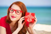Redhead Girl In The Glasses With Gift On The Beach