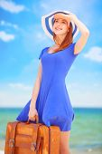 Redhead Girl With Suitcase On The Beach In Spring Time.