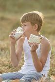 Teenage Farmer Boy Enjoying Fresh Milk And Bread