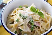Bow ties pasta with ham and green peas