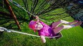 picture of swings  - Happy laughing girl with glasses wearing a pink hat enjoying a swing ride on a sunny summer playground in a home garden - JPG