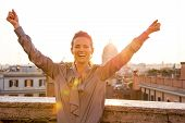 Happy Young Woman Rejoicing On Street Overlooking Rooftops Of Rome On Sunset
