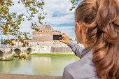 Young Woman Taking Photo Of Castel Sant'angelo In Rome Italy. Rear View