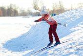 Girl enjoying cross-country skiing down in sunny day