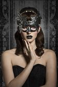 stock photo of mystery  - Mysterious carnival elegant gorgeous female in silver mask with black lips and old fashioned hairstyle - JPG