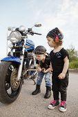 little biker repairs motorcycle on road