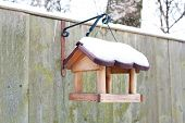Hanging Bird Feeder Covered By Snow In Winter.