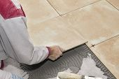 stock photo of overhauling  - Home improvement, renovation - construction worker tiler is tiling ceramic tile floor.