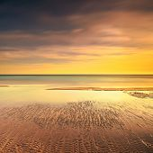 pic of long beach  - Ocean sandy beach line and warm red yellow sunset - JPG