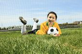 Portrait of young Asian girl with soccer ball.