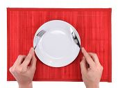 pic of bamboo  - Hands hold fork and knife above plate on bamboo mat - JPG