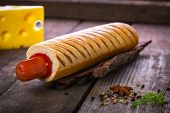 French hot dog grill with ketchup on a wooden surface