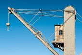 stock photo of crane hook  - A disused small crane with a hook in the harbor of Genoa  - JPG
