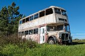 Rusty Abandoned Double-decker Bus Standing In A Field