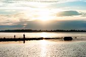 Silhouette Of A Fisherman On The River