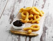 stock photo of churros  - churros with chocolate sweet dessert on a wooden surface - JPG
